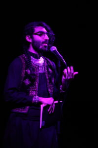 photo of levon kafafian, standing speaking into a microphone on a stage
