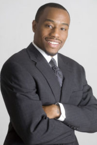 Headshot of Dr. Marc Lamont Hill, smiling, arms crossed